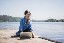 Mujer trabajando en un lago, usando un portátil en un embarcadero - foto de stock