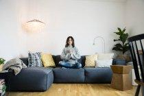 Женщина сидит скрестив ноги на диване с закрытыми глазами, медитируя дома — стоковое фото