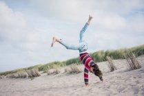 Mature woman having fun, cartwheeling on the beach — Stock Photo