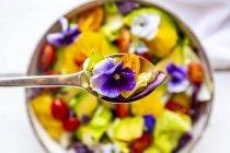 Cuchara de ensalada mixta con aguacate, tomates y flor comestible, primer plano - foto de stock