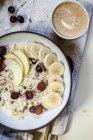 Müslischale mit Bananen, Äpfeln, Trauben, mit Kaffee — Stockfoto