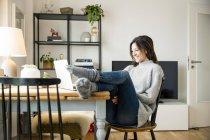 Женщина сидит за столом с поднятыми ногами, используя ноутбук — стоковое фото