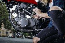 Jovem mulher trabalhando na motocicleta — Fotografia de Stock