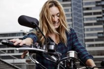 Смеющаяся молодая женщина на мотоцикле — стоковое фото