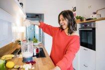 Женщина готовит фруктовый смузи на кухне — стоковое фото