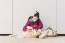 Jovem feliz acariciando e brincando com seu cão golden retriever — Fotografia de Stock