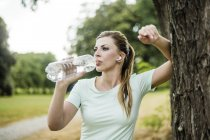 Sportive young woman leaning against a tree in a park and drinking from bottle — Stock Photo