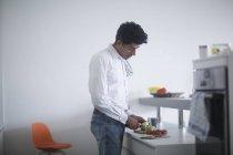 Mann steht in Küche und bereitet Gemüse zum Kochen zu — Stockfoto