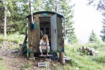 Germany, Bavaria, Oberammergau, smiling young woman sitting in trailer on mountain meadow — Foto stock