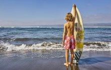 Чилі, Pichilему, хлопчик стояв у морі з дошки для серфінгу — стокове фото