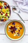Bowl of mixed salad with edible flowers and bowl of creamed pumpkin soup garnished with edible flowers — стоковое фото