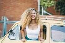 Portrait de femme blonde heureuse penchée par la fenêtre de la voiture classique — Photo de stock