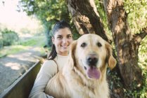 Portrait of a smiling young woman with her Golden retriever dog — Stock Photo