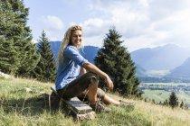 Германия, Бавария, Обераммергау, портрет улыбающейся молодой женщины, сидящей на скамейке на горном лугу — стоковое фото