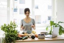 Женщина готовит здоровую пищу на кухне — стоковое фото