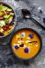 Bowl of mixed salad with edible flowers and bowl of creamed pumpkin soup garnished with edible flowers — Stock Photo