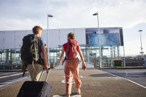 Vista trasera de la pareja caminando fuera del aeropuerto - foto de stock