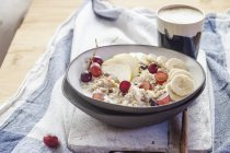 Muesli bowl with bananas, apples, grapes, with coffee — Stock Photo