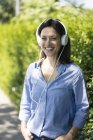 Женщина с наушниками слушает музыку в природе — стоковое фото