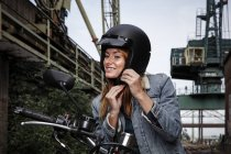 Smiling young woman putting on motorcycle helmet — Stock Photo