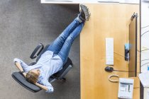 Top view of woman relaxing in chair at desk in office — Stock Photo