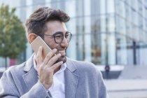 Porträt eines lachenden jungen Geschäftsmannes am Telefon — Stockfoto