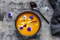 Ciotola di zuppa di zucca cremosa guarnita con fiori commestibili — Foto stock
