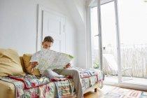 Молодий чоловік, сидячи на дивані вдома і читання карти — стокове фото