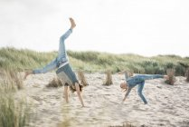 Mother and daughter having fun, cartwheeling on the beach — Stock Photo