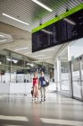 Happy couple walking at the airport with woman waving — Stock Photo