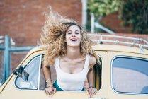 Portrait de femme blonde penchée par la fenêtre de la voiture classique et jetant ses cheveux — Photo de stock