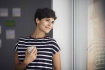 Улыбающаяся женщина с чашкой кофе смотрит в окно — стоковое фото