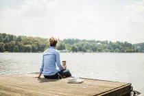 Mujer sentada en el embarcadero en un lago con auriculares y café para llevar - foto de stock