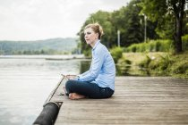 Woman sitting on jetty at a lake and using tablet — Stock Photo
