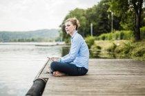 Mujer sentada en el embarcadero en un lago y usando una tableta - foto de stock