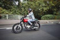 Молодая женщина на мотоцикле по улице — стоковое фото