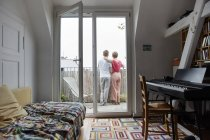 Rear view of couple standing on balcony at home — Stock Photo