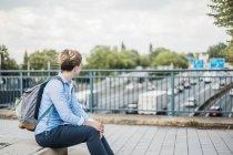 Mulher com mochila sentado na ponte da auto-estrada — Fotografia de Stock