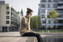 Donna al telefono seduta sulla panchina in autunno — Foto stock