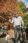 Портрет людини на вулиці з собакою і велосипедом, жестами світу пальцями — стокове фото