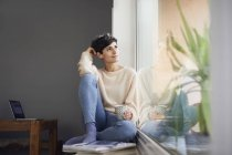 Relaxed woman at home sitting at the window — Stock Photo