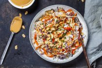 Warm rice salad with grated vegetables, peanut sauce and peanuts — Photo de stock