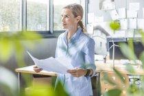 Frau im Amt arbeitet an Plan mit Windrad-Modell auf dem Tisch — Stockfoto
