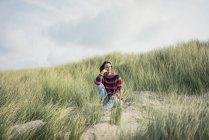 Зрелая женщина отдыхает на пляже, сидит в дюнах — стоковое фото