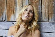 Retrato de mulher loira feliz na frente da parede de madeira — Fotografia de Stock