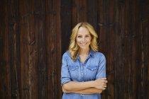 Retrato de mulher loira sorridente na frente da parede de madeira — Fotografia de Stock