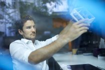 Portrait of young man behind windowpane examining prototype — Stock Photo