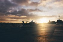 Helicopter on landing place during sunset — Stock Photo