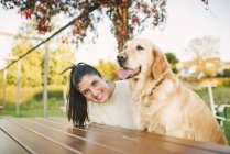 Portrait of happy young woman with her Golden retriever dog resting in a park — Stock Photo