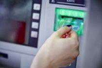 Крупный план женщины, помещающей карту в игровой автомат — стоковое фото